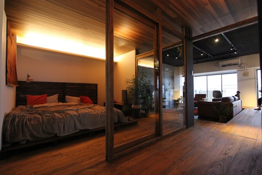 廊下に入ると      左手にはガラスパーテーション越しに      寝室のベッドが見えます          ポイントとして      天井と床が      リビング・寝室・廊下の空間ごとに      仕切られていない事です