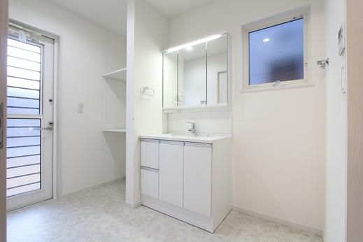 キッチンの奥には      3帖の洗面脱衣室があります      収納もあるゆとりのある脱衣室      部屋干しスペースとしても活かせます          また、この部屋の勝手口は      南の庭にも直接アクセス可能です      お庭の一部にウッドデッキをつくり      外干しも1階で実現できます