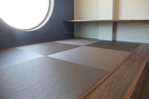 そしてTVの壁の反対側には      畳ベンチが設置されています      このベンチに腰掛け      TVを見ながら家族と会話を            お疲れの時には      この畳の上で寛ぎ      横になってTVも見れます            カウンターも設置され      お子様が勉強したり      パソコンを利用したり      実用的なスペースとなっています          そして外観のシンボルとなる      丸窓からの光がまぶしく      居心地の良い空間が生まれました